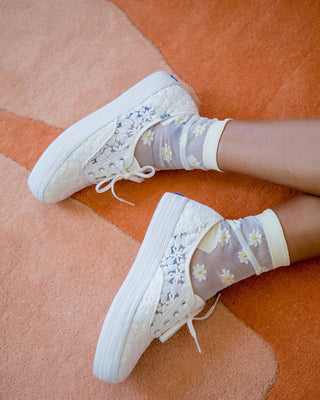 white sheer socks with daisy embroidery shown on woman's feet with white daisy patterned sneakers