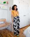 model wearing mustard ruffle edge cardigan with cow print pants