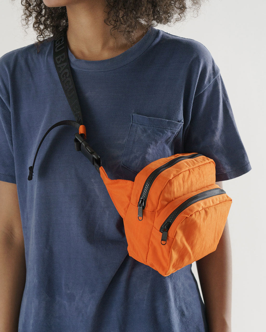 model shown with orange fanny pack as a cross body bag