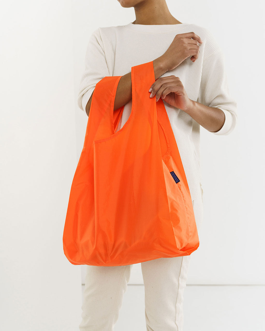 model shown holding orange baggu
