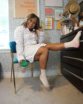 model shown wearing long sleeve party dots dress sitting down