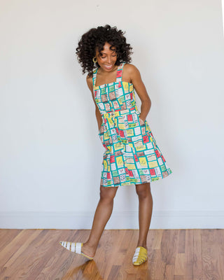 woman wearing multicolored dress with matchbox pattern and yellow and white slides