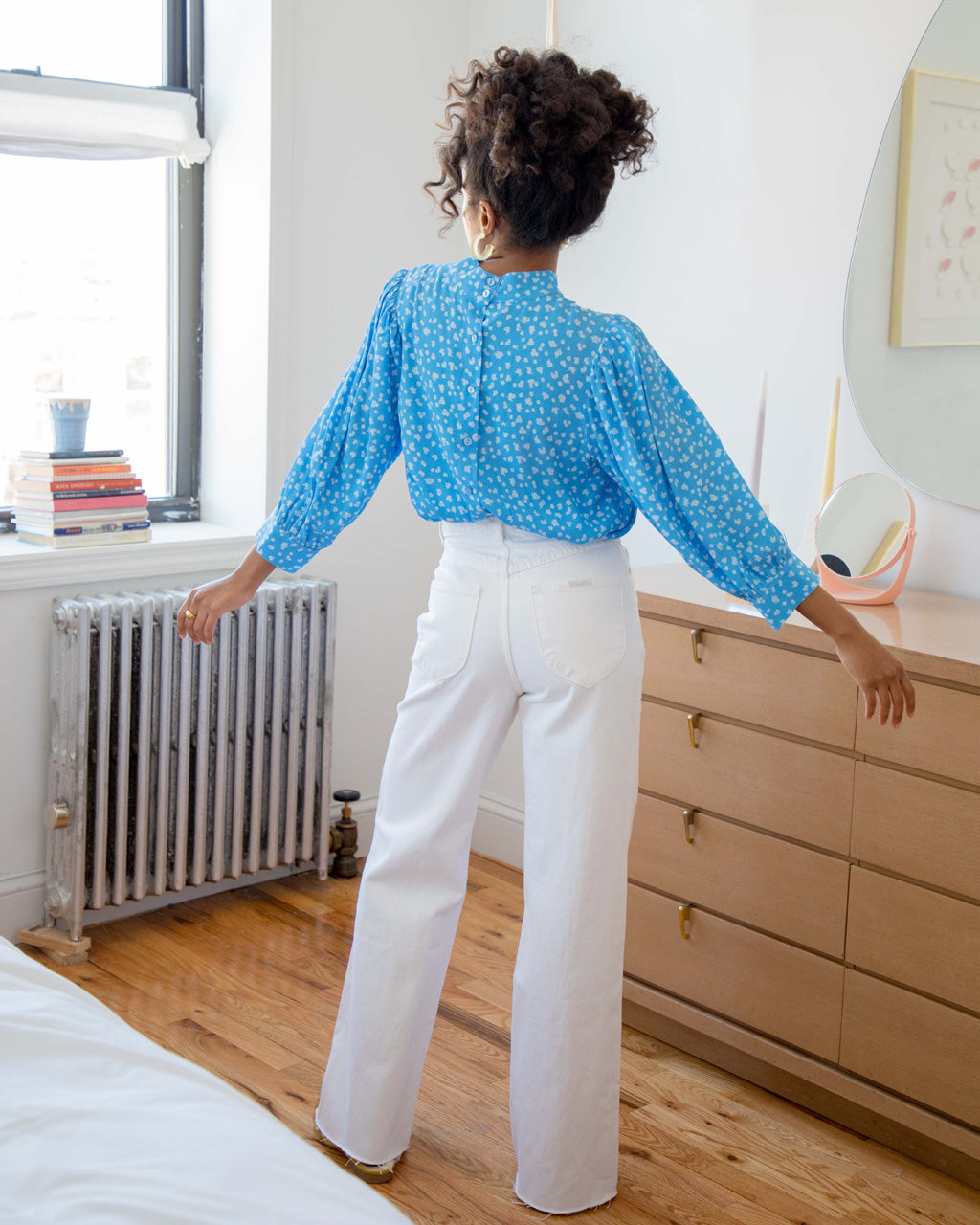 back view of woman wearing blue daisy print long sleeve blouse with white jeans