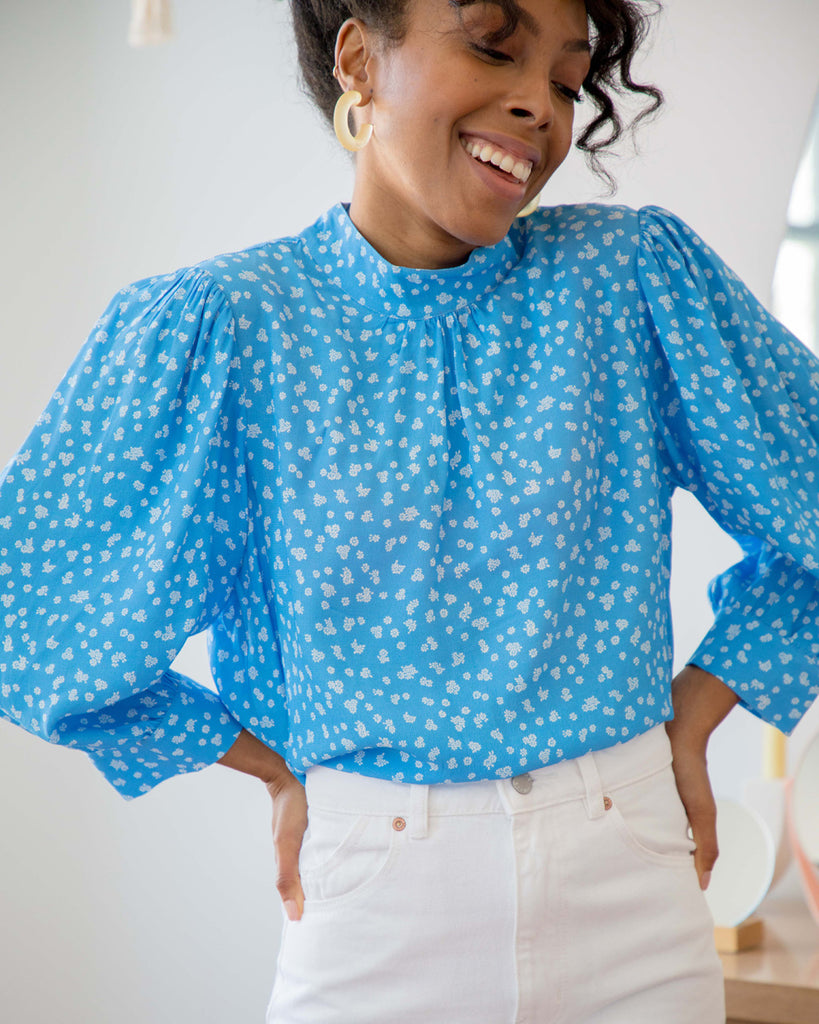 woman wearing blue daisy print long sleeve blouse with white jeans