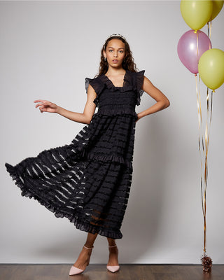 model shown wearing black ruffle midi dress with light pink heels
