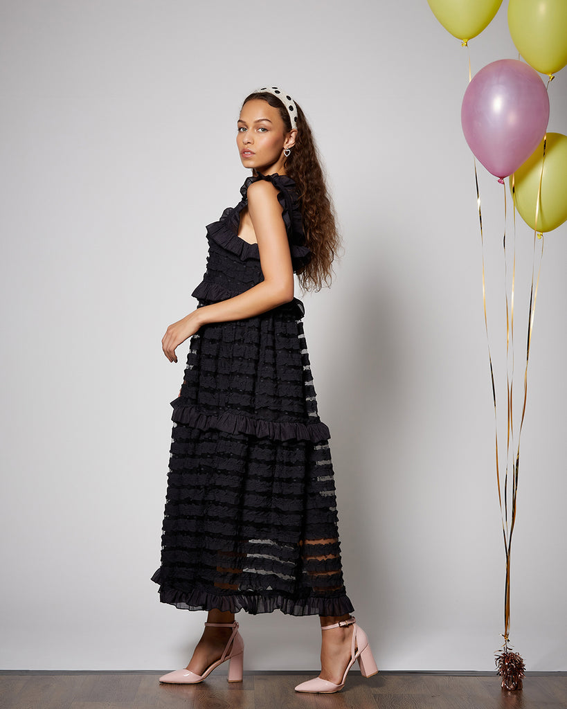 model shown wearing black midi ruffle dress