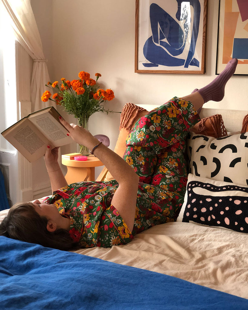 brunette model laying down reading a book wearing emerald super bloom leisure shirt with matching pants