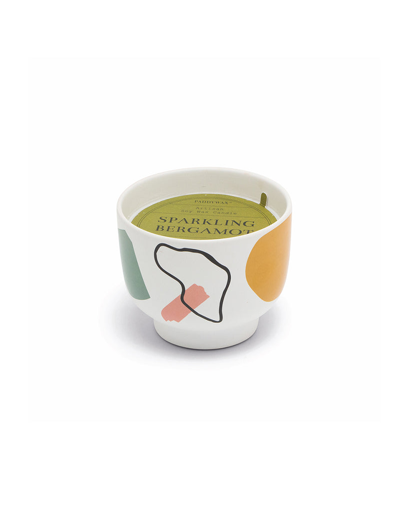 white vessel candle with abstract art design and green label