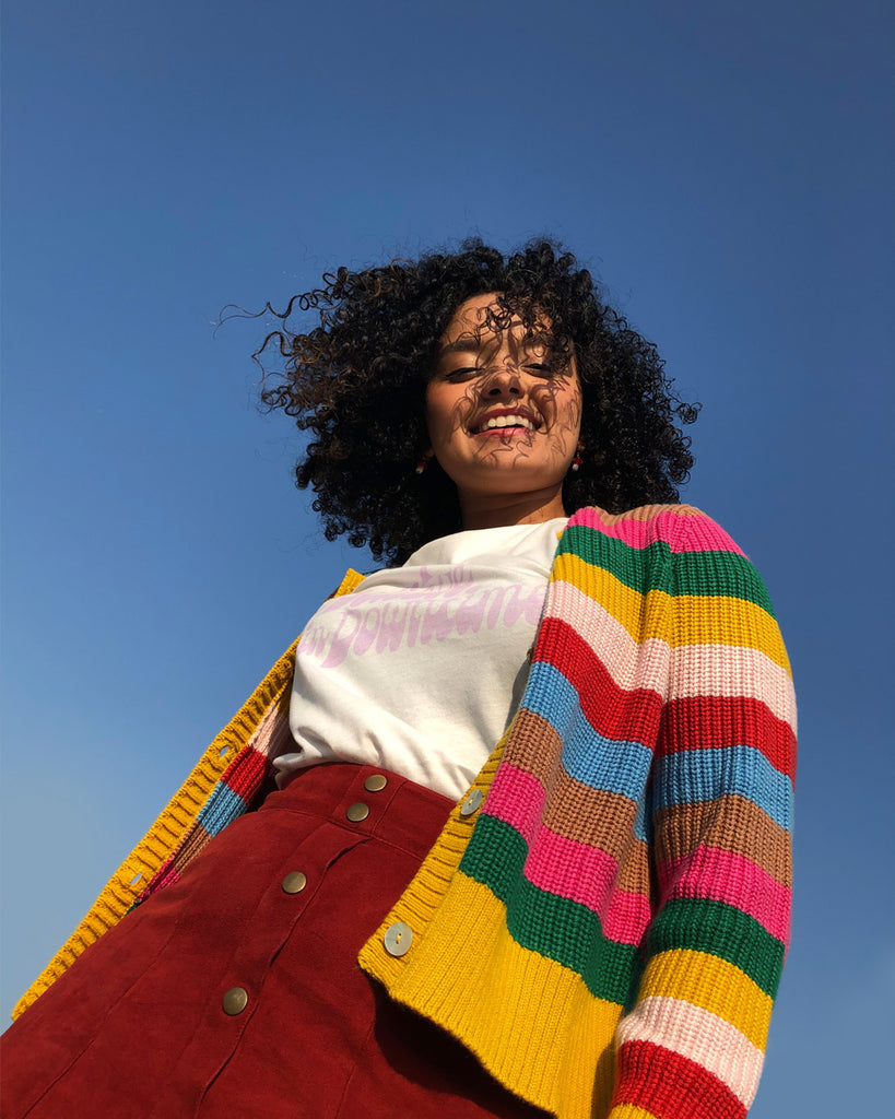 girl standing against a blue sky, wearing a striped cardigan
