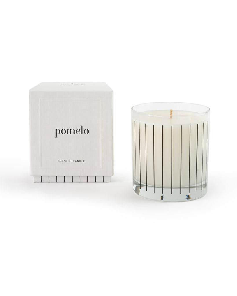 The Pomelo candle by Studio Stockhome is white and comes in a clear glass tumbler with black vertical stripes.