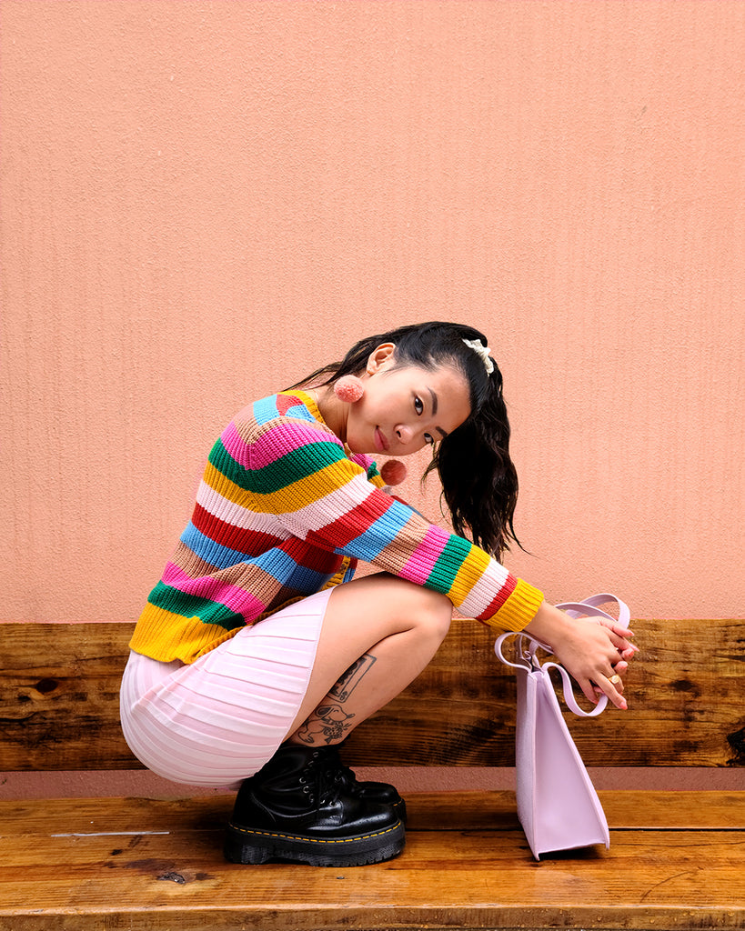model shown wearing sunset stripe cardigan paired with a pink skirt