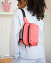 model wearing light blue jacket with match shorts and watermelon pink baggu fanny pack over her shoulder