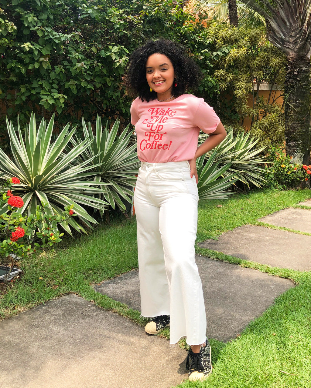 girl on a sidewalk, surrounded by plants, wearing white jeans and a pink t-shirt