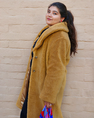 model shown wearing a mustard colored sherpa jacket