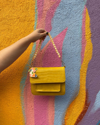 yellow cayman yellow bag shown in front of a colorful wall