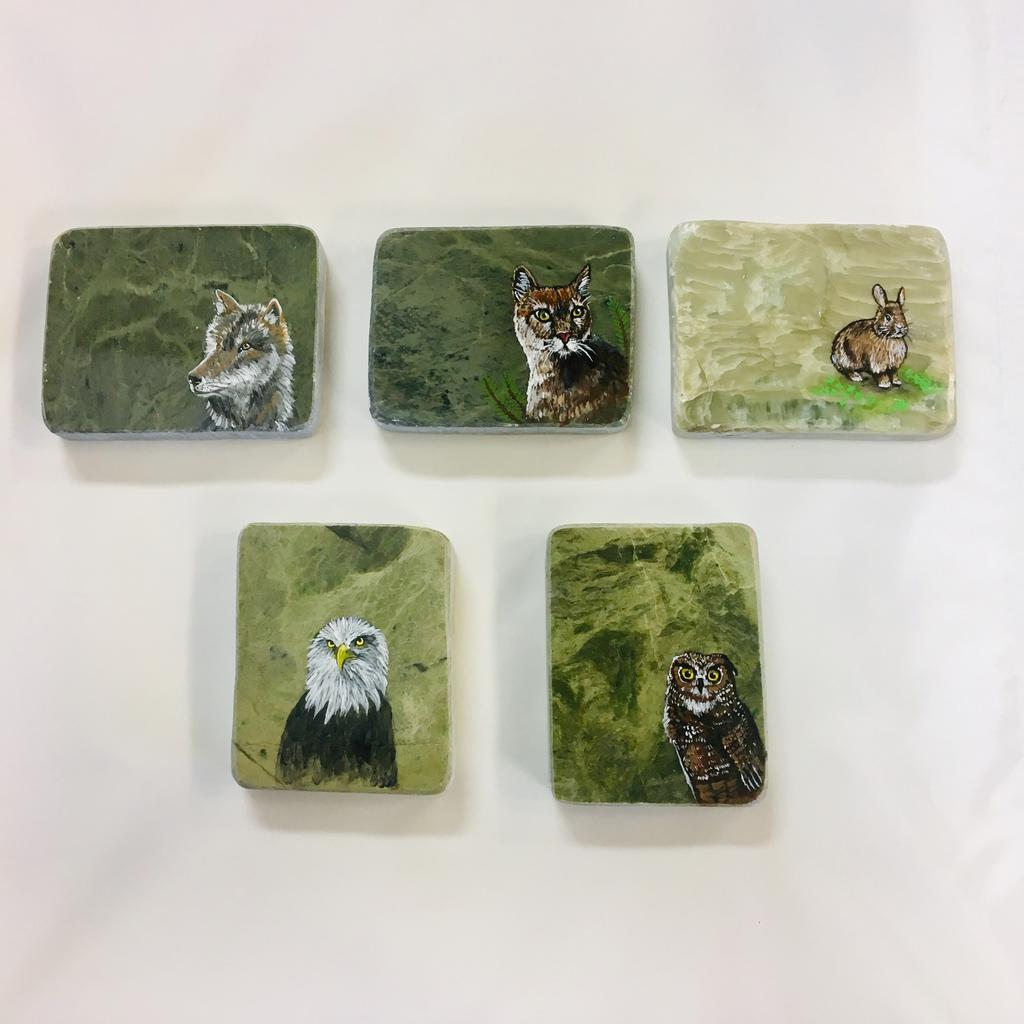 Assorted paintings on jade slabs, hand painted in Jade City.