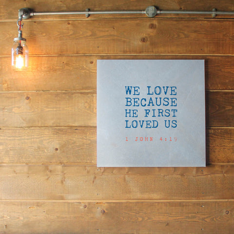 Contemporary love themed Christian wall art featuring scripture verse from 1 John. 'We love because he first loved us'. Bold blue design on a light blue background. Printed on quality canvas and hand-stretched. 4 sizes. Free Delivery.
