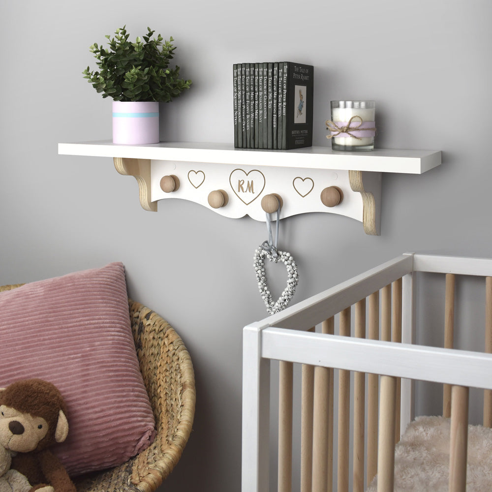 Nursery room scene with new baby nursery shelf with wooden hanging knobs.