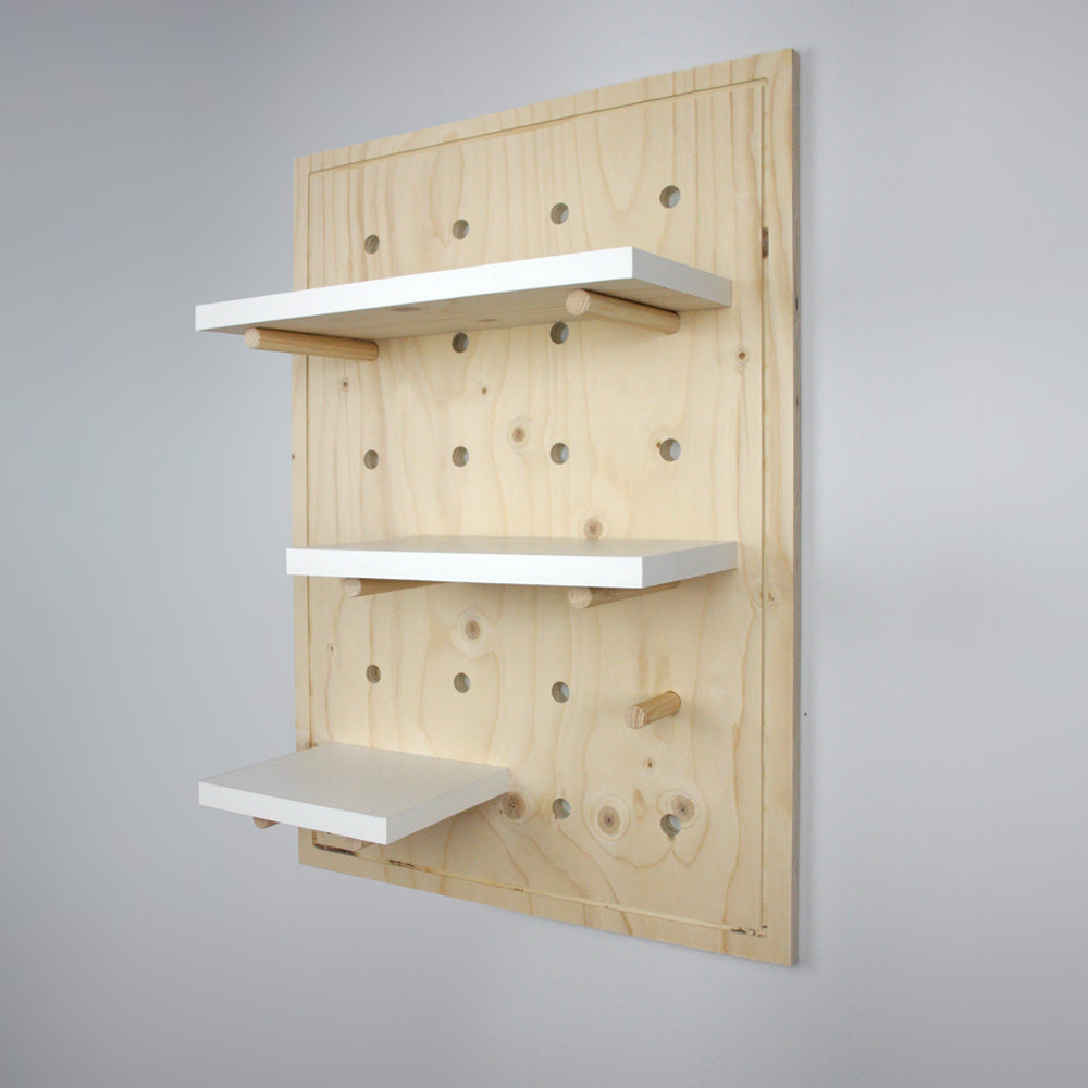 Nursery pegboard wall mounted shelving unit without anything displayed.
