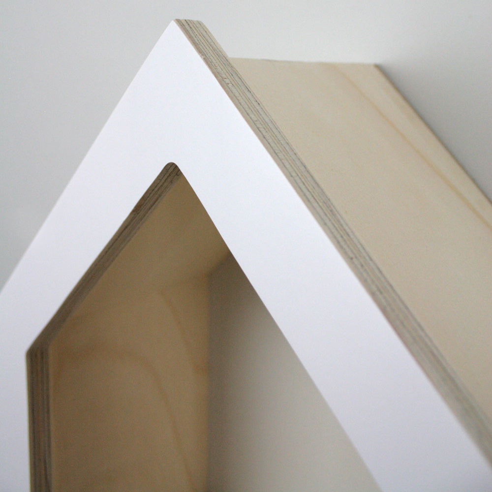 Nursery themed house shaped wall mounted shelf close up top detail.