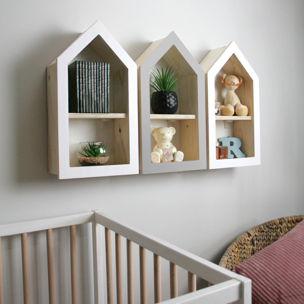 Nursery themed house shaped wall mounted shelf in nursery room setting.