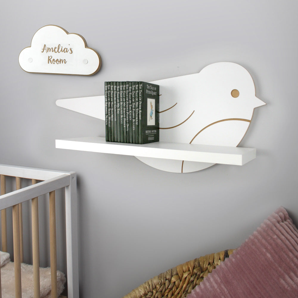 Nursery themed bird shaped wall mounted shelf in a nursery room setting with added themed cloud plaque.