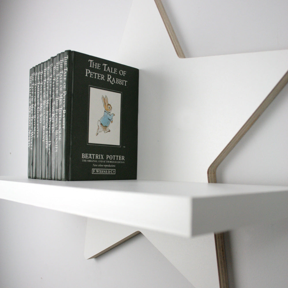Nursery themed star shaped wall mounted shelf with books and top shelf detail.
