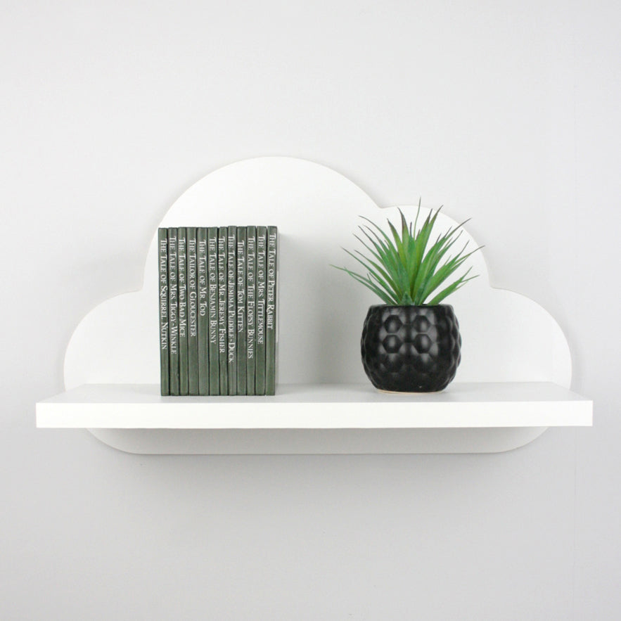 Nursery themed cloud shaped wall mounted shelf with books and plant.