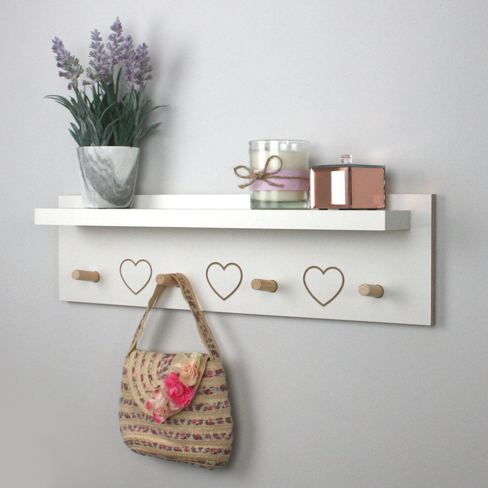 Mounted white ledge shelf with wooden pegs and engraved hearts.