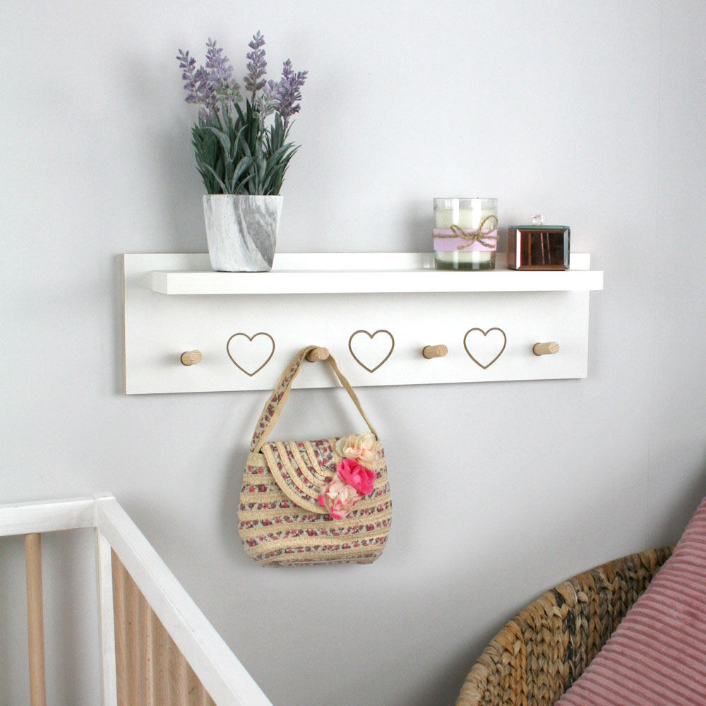 Floating shelf with coat hangers mounted in nursery.