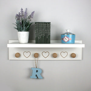 Floating shelf with engraved harts and hangers