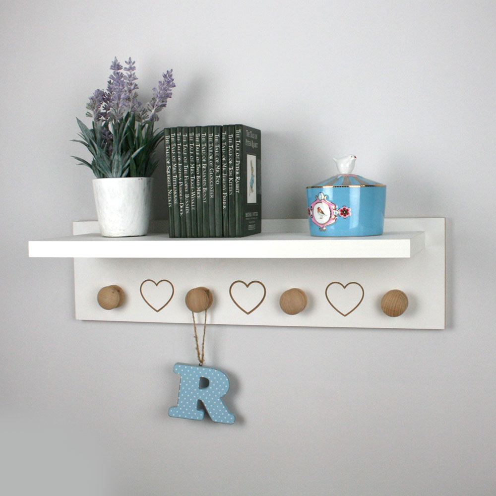 Floating shelf with engraved hearts and hangers mounted on nursery wall.