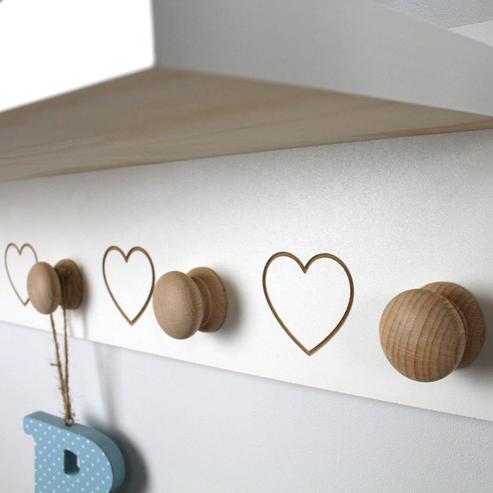 Engraved shelf heart detail with wooden knobs.