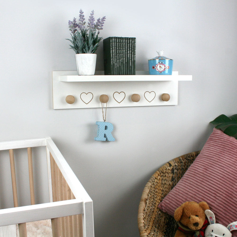 shelf with hearts and hangers mounted in nursery.