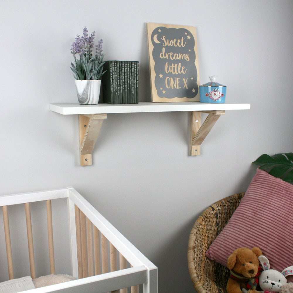 Wooden bracket shelf mounted on nursery wall.