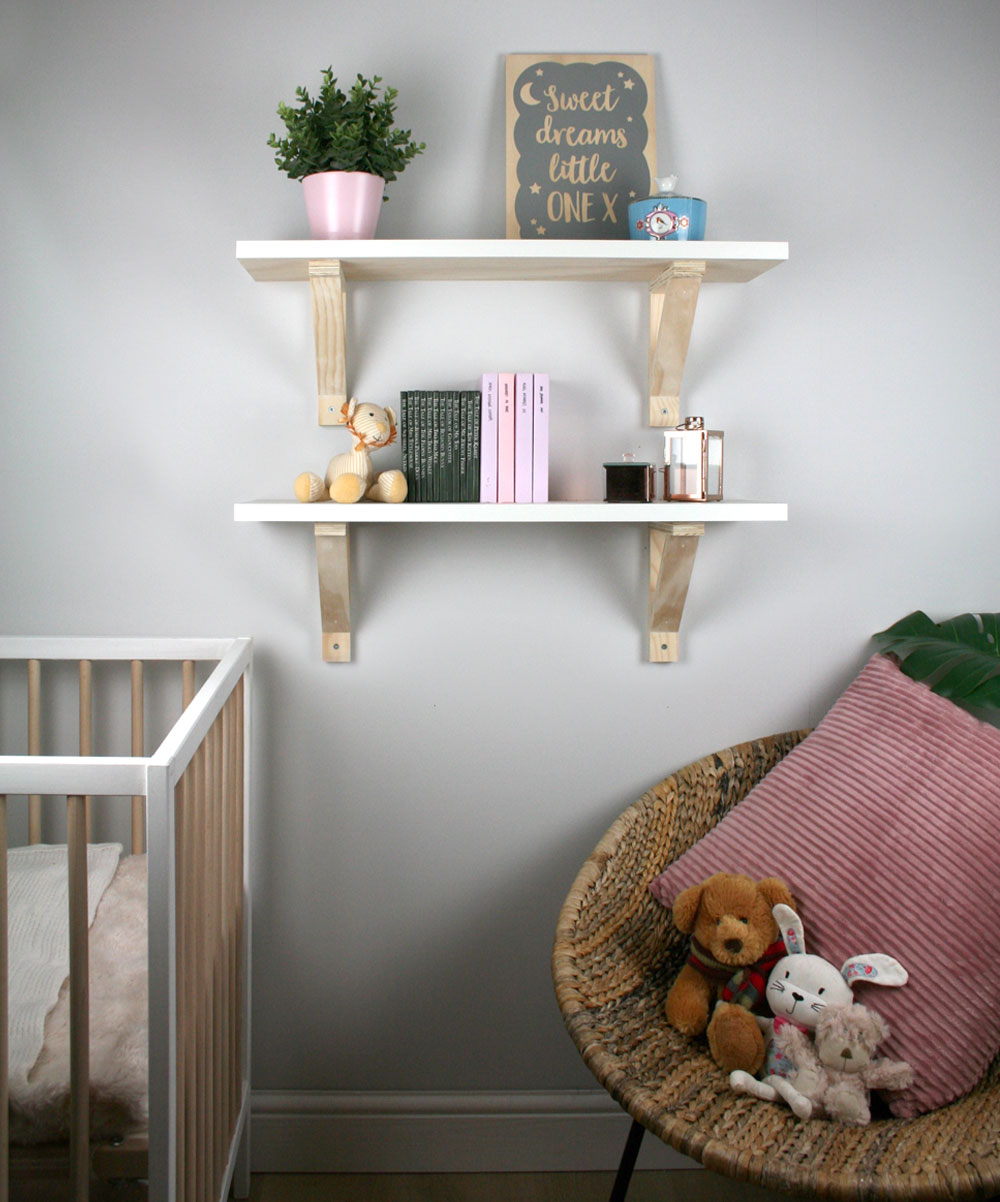 Two shelfs with wooden brackets mounted on nursery wall.