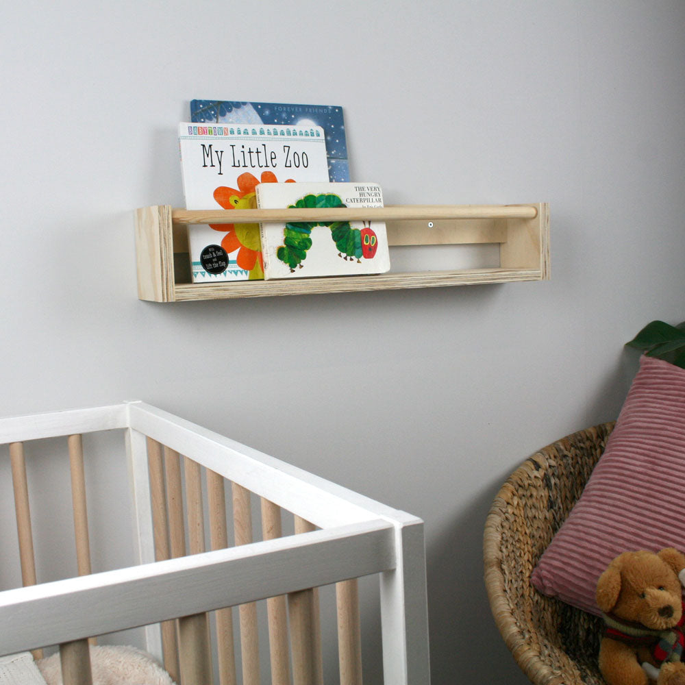 Wooden book rack mounted on nursery wall.
