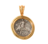 An ancient Greek silver coin featuring the Boy on Dolphin.  Reverse face shows a naked youth on horseback. The coin is set in a 14kt gold polished bezel mounting the size of a U.S. quarter with an 11mm tapered hinged bail. Each mounting is handcrafted to fit the coin precisely and protect it's historical value. Denomination: Diadrachm Date: c. 290 B.C. Mint: Calabria, Taras Coin comes with a Certificate of Authenticity Item #8626