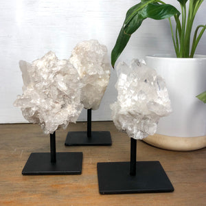 Clear quartz crystal cluster with statue stand - various