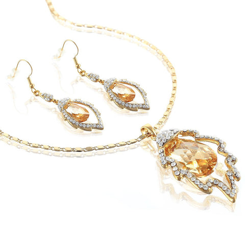 Contemporary Swarovski Elements Crystal Pendant Necklace & Earrings Set. Single 20mm Swarovski Cut Crystal Suspended within a Leaf, Studded with Clear Crystals. Amethyst on Silver Rhodium, Light Colorado Topaz on 14k Gold, Replica Matching Earrings.