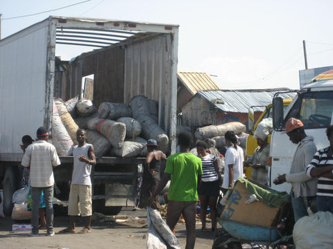 Charcoal being delivered to markets in Port Au Prince Haiti. This is harvested deep in the mountains and hauled by boat and truck to urban markets to fulfill cooking needs. Each bag costs $6US and will only last 30 days on average. – B. Trauth