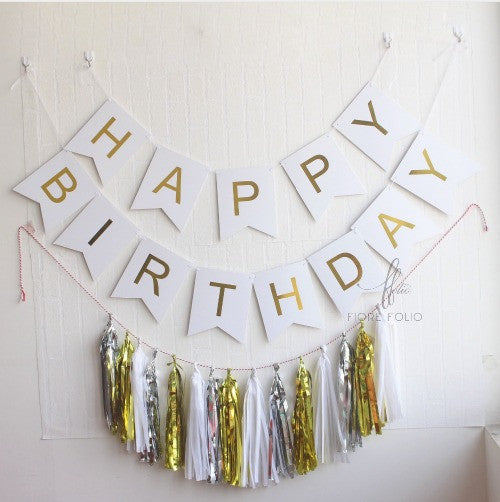 white and gold birthday themed decor. birthday banner and tassels