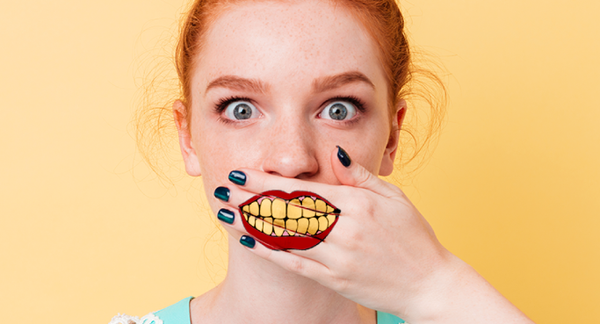 woman covering her mouth with her hands which has a mouth with a yellow teeth painted on it