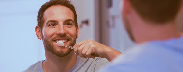 Close-up image of a man brushing his teeth and smiling while standing against a mirror