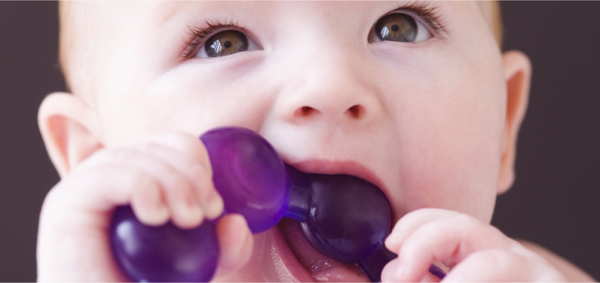 Baby chewing on teething ring toy