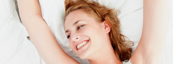 young woman smiling while lying in the bed