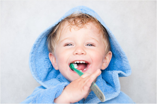happy kid brushing his teeth with Radius organic toothbrush for kids