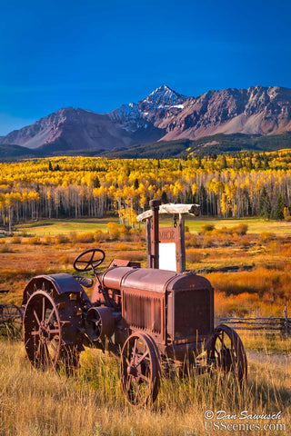 an old tractor sits in front of wilson peak and yellow fall aspens near telluride colorado