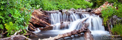 A panoramic photo of a waterfall in the summer