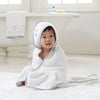 baby in bathroom wrapped in aden and anais hooded classic towel in twinkle